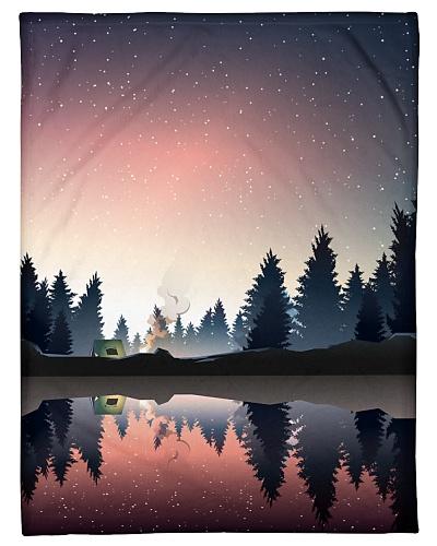 Camping in pine wood near lake at dusk